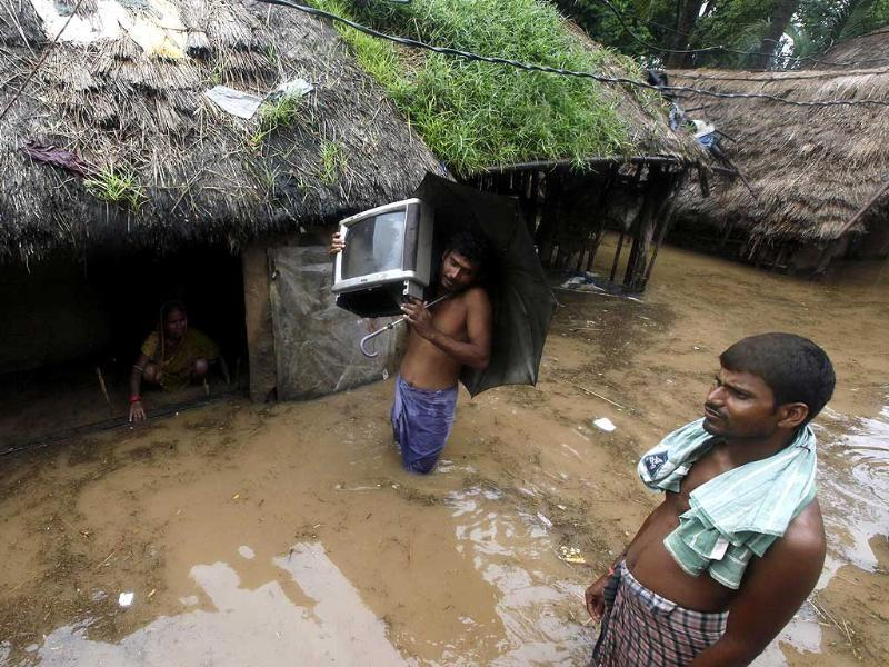 A man takes a television to a safe place after his house floods with rain water in Srirampur village, Odisha, India. (Raj K Raj/HT Photo)