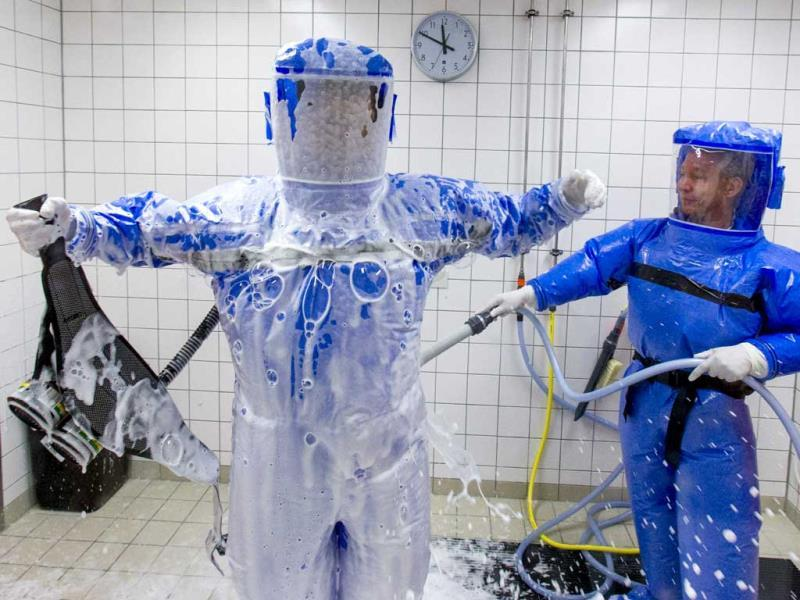 Ward physician Thomas Klotzkowski (R) cleans Dr Florian Steiner, in a disinfection chamber at the quarantine station for patients with infectious diseases at the Charite hospital in Berlin. (Reuters Photo)