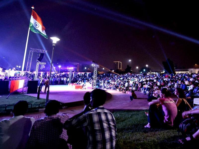 People enjoy music as the national flag flatters during the inauguration of the week-long celebrations of Independence Day at the Central Park in New Delhi. PTI Photo