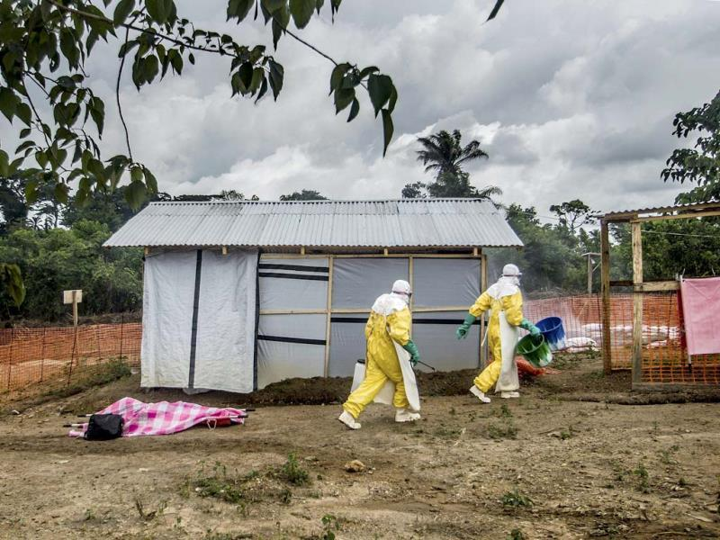 Health workers in protective suits prepare to transfer the body of an Ebola victim to the morgue at the MSF Ebola treatment center in Kailahun, Sierra Leone. (AP Photo)