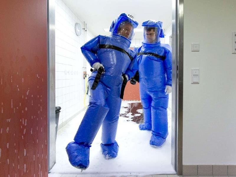 Doctor for tropical medicine Florian Steiner (R) and ward physician Thomas Klotzkowski step out of a disinfection chamber after cleaning their protective suits, at the quarantine station for patients with infectious diseases at the Charite hospital in Berlin. (REUTERS Photo)