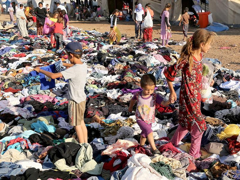 Displaced Iraqis from the Yazidi community look for clothes to wear among items provided by a charity organization at the Nowruz camp, in Derike, Syria. (AP photo)