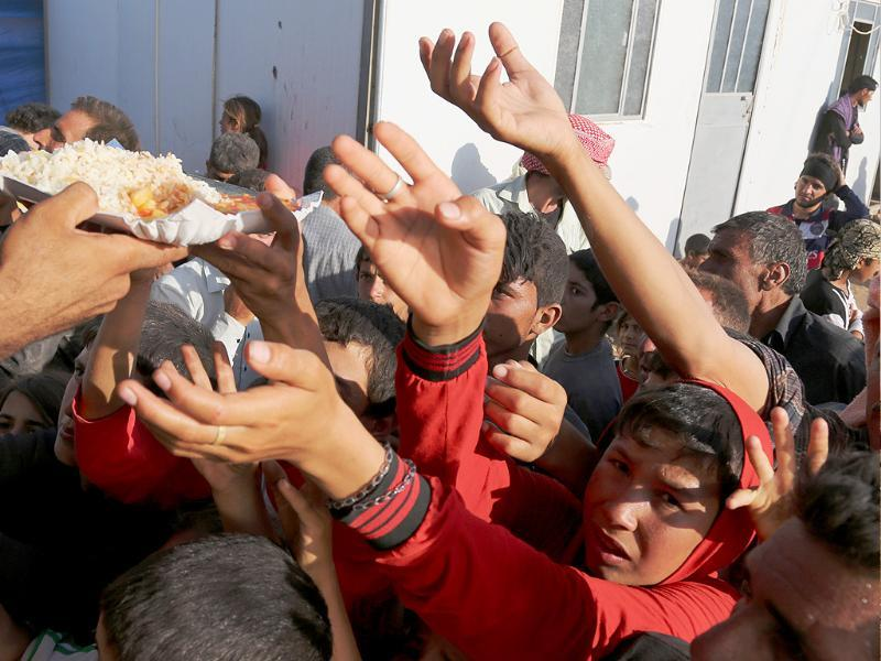 Displaced Iraqis from the Yazidi community gather for food at the Nowruz camp, in Derike, Syria. (AP photo)