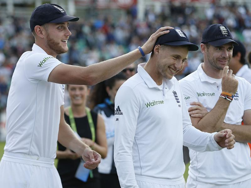 England's Stuart Broad (L) pats the head of teammate Joe Root (C) as James Anderson looks on, after they defeated India in the final of the five-Test series 3-1, at The Oval in London. (AP Photo)
