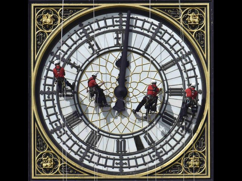 Cleaners abseil down one of the faces of Big Ben, to clean and polish the clock face, above the Houses of Parliament, in central London August. (Reuters)