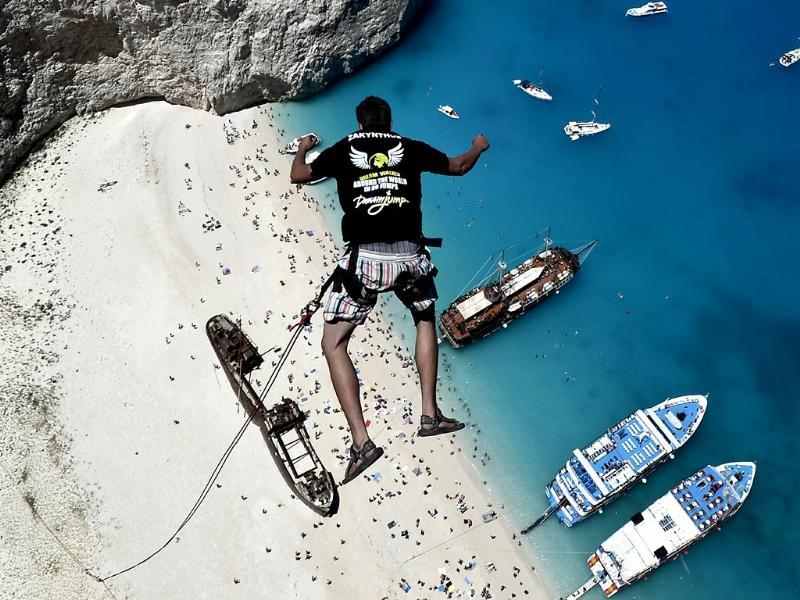 Lukas Michul, a member of the 'dream walker' group jumps from atop the rugged rocks overlooking the azure waters of Navagio beach, one of the Greece's most renowned leisure spots on the popular tourist island of Zakynthos. (AFP Photo)