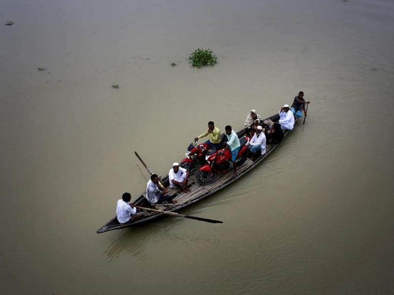 Villagers sail on a boat through a flood-affected area in Ashigarh village, about 70 kilometers east of Guwahati. (AP Photo)