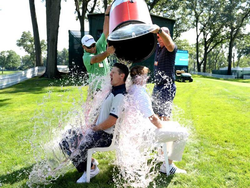 Golfers Justin Rose of England and Brandt Snedeker of the USA take the 'ice bucket challenge' with a bit of help from their caddies Mark Fulcher and Scott Vale. (AFP Photo)