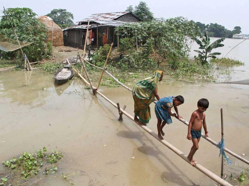 Villagers use a makeshift bamboo bridge to move across flooded areas of Morigaon district in Assam. (Reuters Photo)