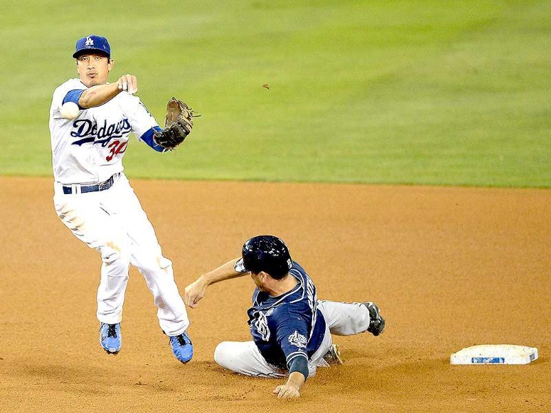 Darwin Barney #30 of the Los Angeles Dodgers turns a double play in front of Seth Smith #12 of the San Diego Padres during the fifth inning at Dodger Stadium. (AFP Photo)