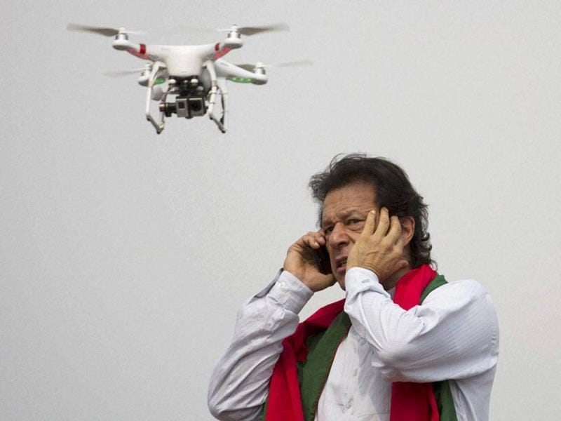Pakistan's cricketer-turned-politician Imran Khan talks over a phone as a camera-equipped drone hovers outside a parliament in Islamabad. (AP Photo)