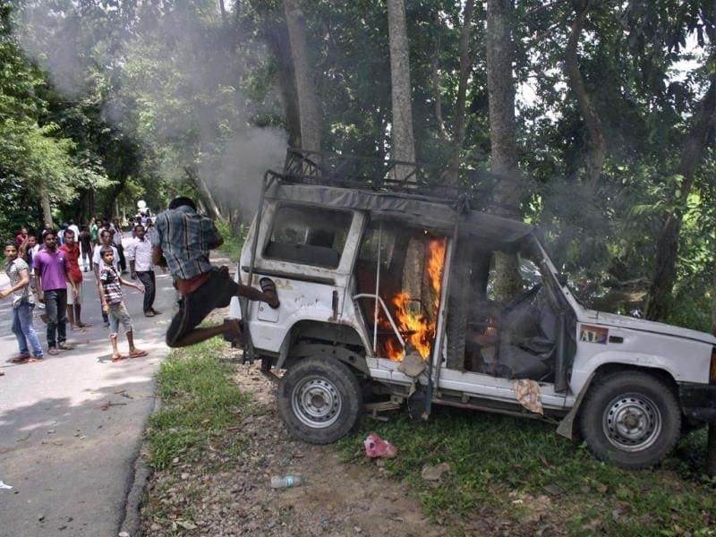 A demonstrator kicks a vehicle that was set on fire during a protest at Golaghat district in the northeastern Indian state of Assam. (Reuters Photo)