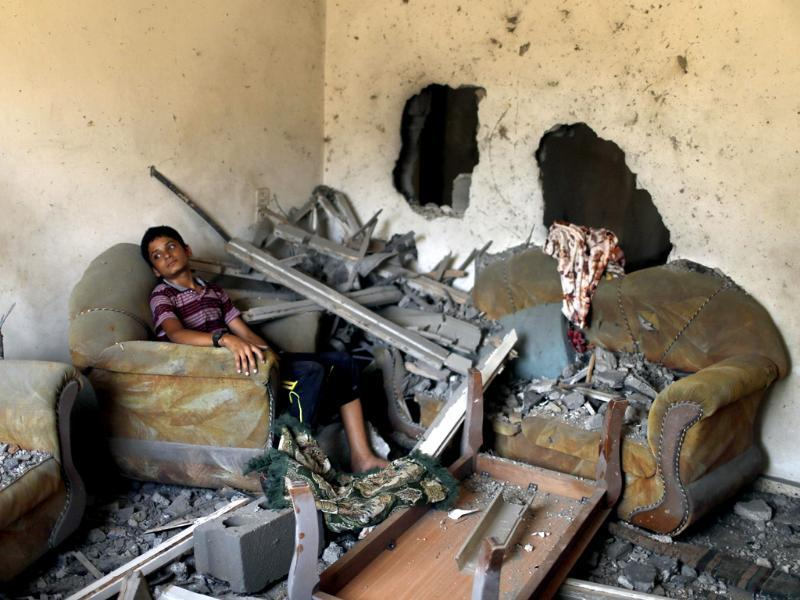 A Palestinian boy sits in his house, which witnesses said was damaged in an Israeli air strike, in Gaza City. (Reuters Photo)
