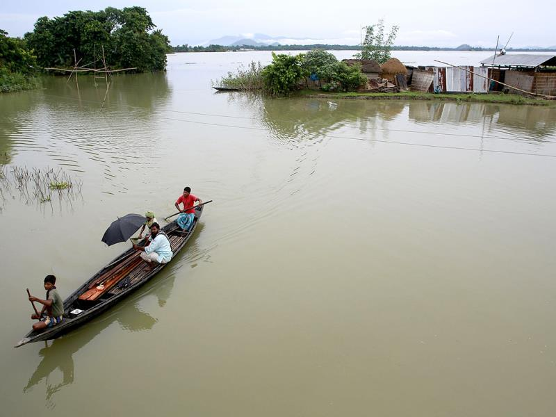 A villagers row a country boat past houses cut off by flood waters at Ashigarh village in Morigaon district of north eastern Assam state, India. (AP Photo)
