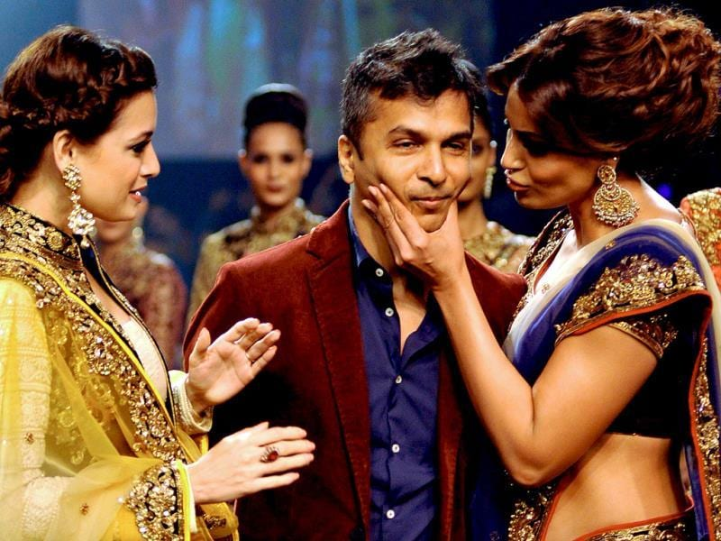 Bollywood actress Dia Mirza (L) and Bipasha Basu (R) interact with designer Vikram Phadnis (C) as they showcase his creations in collaboration with Nakkashi during the Lakme Fashion Week (LFW) Winter/Festival 2014 in Mumbai. (AFP Photo)