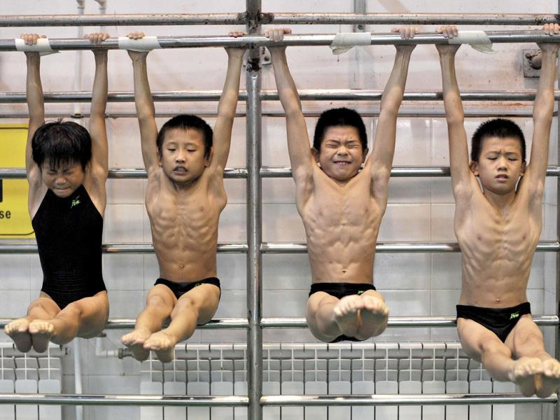 Young divers stretch as they hang from a steel bar during a training session at a sports school in Hefei, Anhui province. (Reuters Photo)