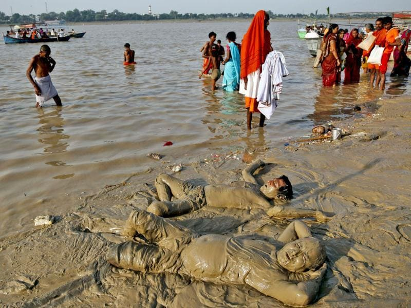 Hindu devotees lie down with their bodies covered with mud for cooling effect on the shore of the River Ganges at Sangam, the confluence of rivers Ganges, Yamuna, and mythical Saraswati on the auspicious occasion of Somvati Amavasya in Allahabad. (AP photo)