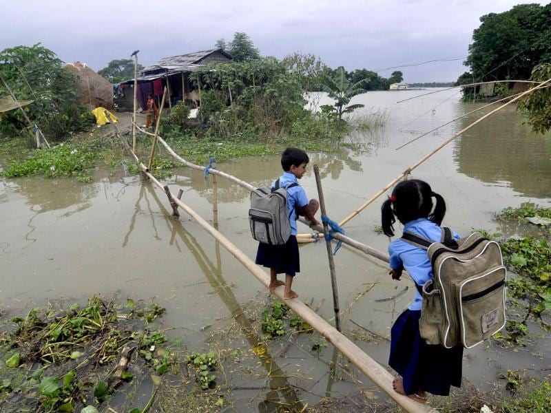 Schoolchildren use a bamboo bridge to cross floodwaters in Morkata village in the Morigoan district of Assam. (AFP photo)