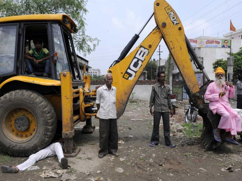 Protestors stand in front of the JCB machine during an anti-encroachment drive near Vijaynagar crossing, in Indore on Tuesday. (Amit K Jaiswal/HT photo)