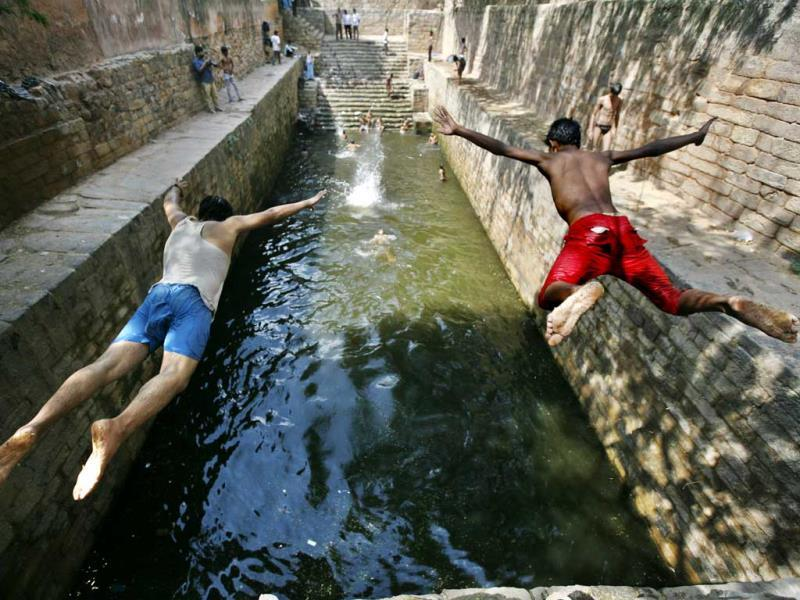 Boys jump into a Baoli (step-well) called Gandhak Ki Baoli in Mehrauli, Delhi. (Arun Sharma/HT Photo)