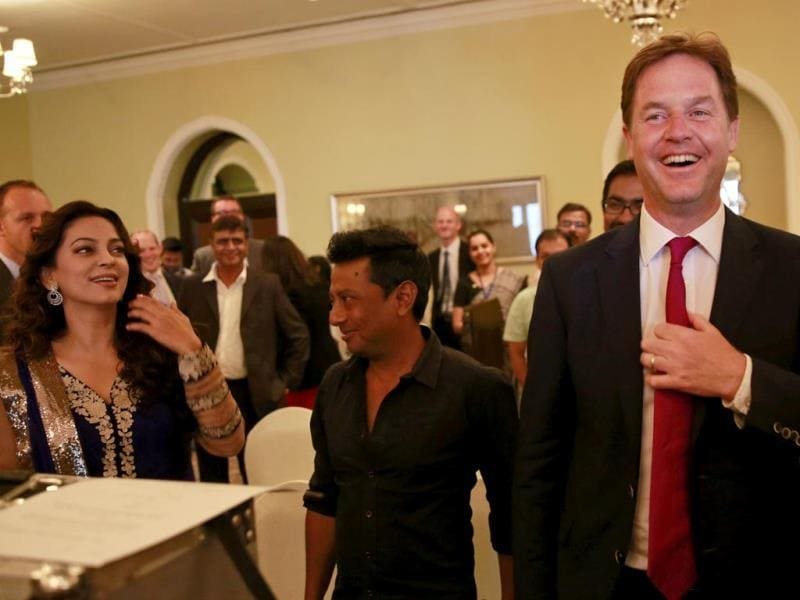 Britain's Deputy Prime Minister Nick Clegg laughs as Juhi Chawla watches on at the muhurat shot of Onir's Veda. (AP Photo)