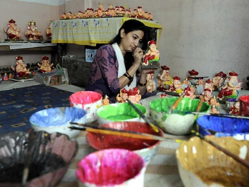 A woman gives finishing touches to Ganesh idols in Indore as the city gears up to celebrate Ganesh Chaturthi. (Arun Mondhe/HT photo)