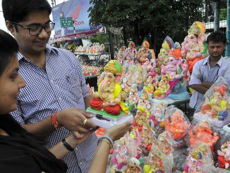 Buyers look at a colourful Ganesh idol at a stall at Board Office Square in Bhopal. (Praveen Bajpai/HT photo)