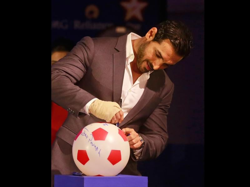 John Abraham, Bollywood actor and co-owner of NorthEast United FC, signs a soccer ball during the official launch of the Indian Super League (ISL) in Mumbai on August 28, 2014. The eight-city franchise-based ISL tournament is to be played in October-December. (AP/Rafiq Maqbool)