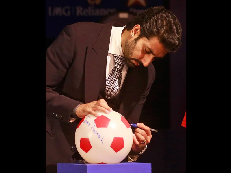 Abhishek Bachchan signs a soccer ball during the official launch of the Indian Super League.