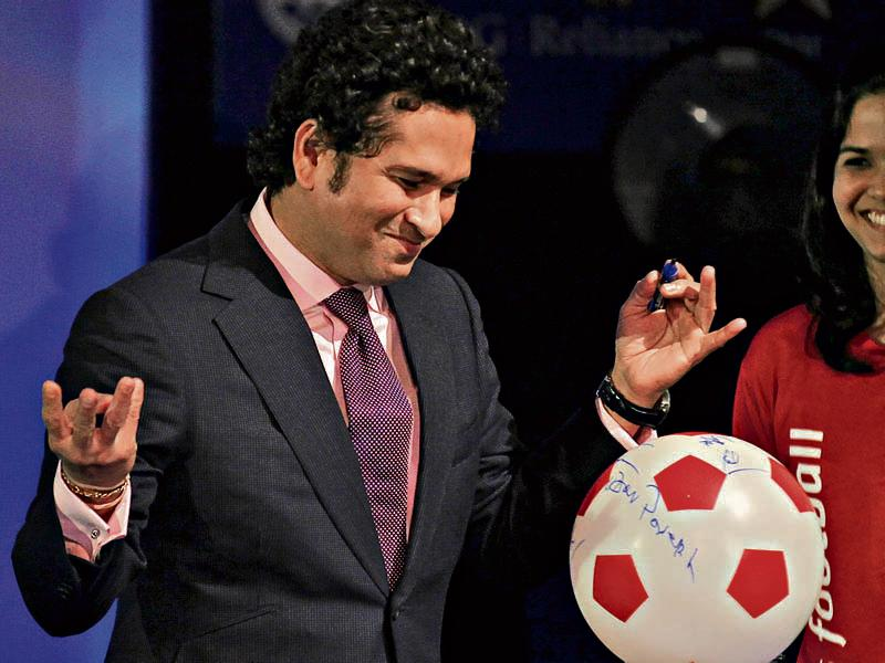 Retired cricketer and co-owner of the Kerala Blasters soccer team Sachin Tendulkar signs a soccer ball replica during the emblem-unveiling ceremony of the Indian Super League at Hotel Trident in Mumbai on August 28, 2014. (Hindustan Times/Vijayanand gupta)
