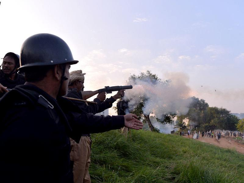 A Pakistani riot policeman fires a tear gas shell on the supporters near Nawaz Sharif's residence in Islamabad on Sunday. At least 300 people were wounded in clashes between the police and protesters, according to hospital officials, as a fortnight-long political impasse took a violent turn. (AFP PHOTO)