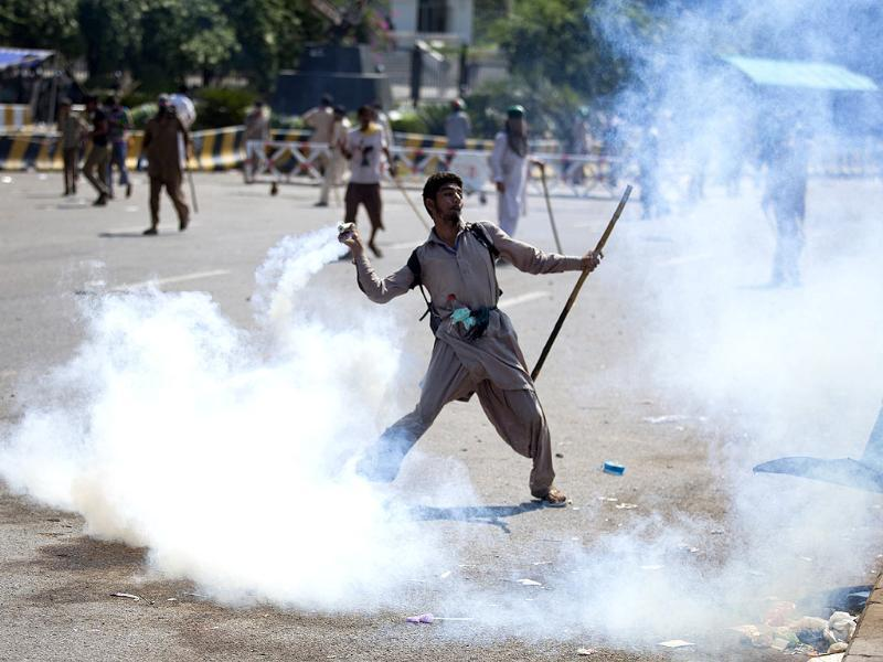 A Pakistani protester throws tear gas shell back towards the police in Islamabad on Sunday. (AP Photo)