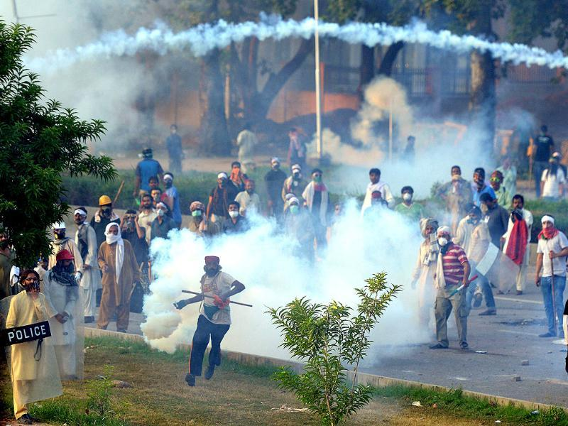 A Pakistani supporter of Tahir ul Qadri (C) throws a tear gas shell towards the police during clashes with security forces near the PM's residence in Islamabad on Sunday. (AFP PHOTO)