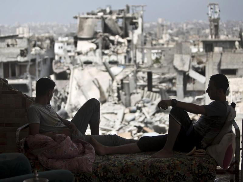 Palestinians sit inside their destroyed house after returning home in the Tufah neighbourhood in eastern Gaza City. (AFP Photo)