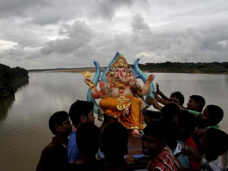 Devotees prepare to immerse an idol of Lord Ganesha into river Kuakhai after worshiping it during the Ganesh Chaturti festival on the outskirts of Bhubaneswar. (AP Photo)