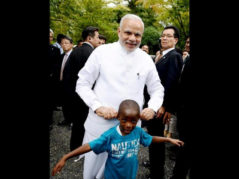 Prime Minister Narendra Modi shares a light moment with a child during his visit at Golden Pavilion, Buddhist temple in Kyoto, Japan. (PTI Photo)