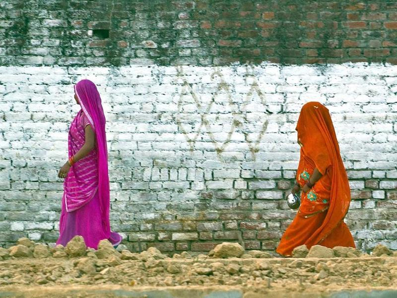 In this photograph residents return after defecating in an open field in a village in the Badaun district of Uttar Pradesh. (AFP Photo)