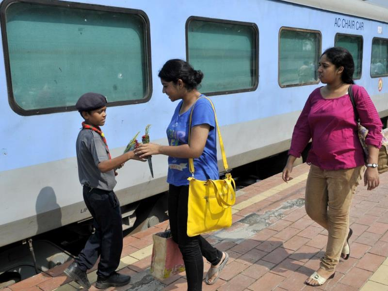 A scout guide cadet presents a flower to a passenger who was boarding Shatabdi Express from Habibganj railway station, in Bhopal on Monday. (Praveen Bajpai/HT photo)