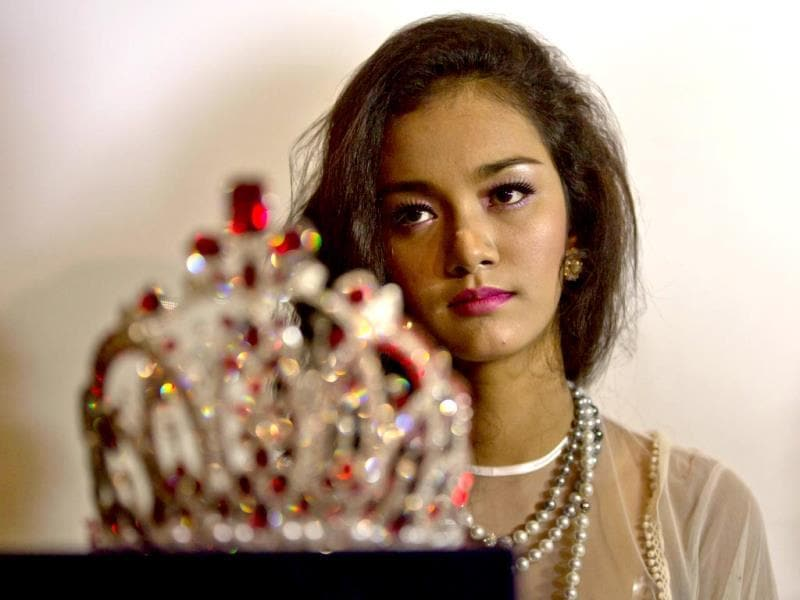 May Myat Noe, Myanmar's first international beauty queen, winner of 2014 Miss Asia Pacific World sites in the background of $ 100,000 worth crown that she allegedly ran away with, during a press conference in Yangon, Myanmar.(AP Photo)