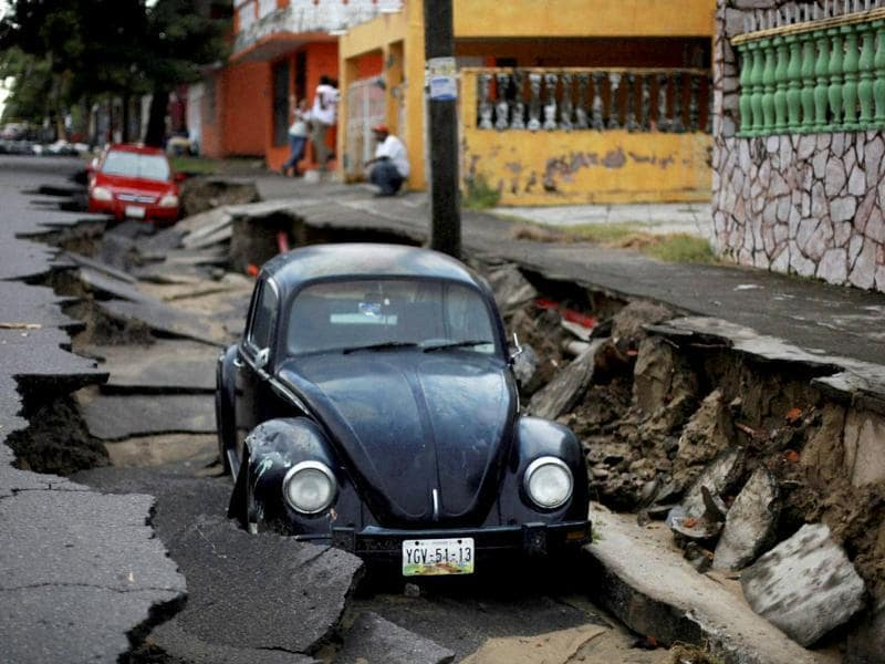 A couple of cars lie in a portion of a collapsed street due to heavy rains in the Gulf port city of Veracruz. (AP Photo)