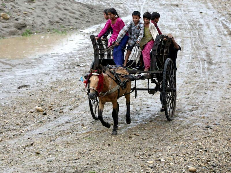 Children ride a horse cart on the banks of the river Tawi as it rains in Jammu. (Reuters Photo)