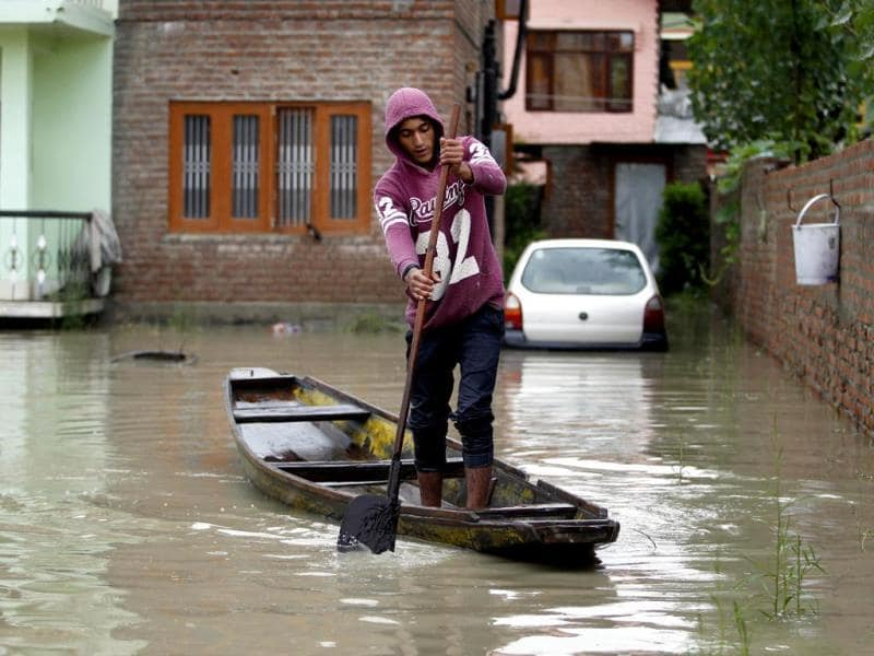 A Kashmiri boy rows a boat in the front lawns of a submerged house in a flooded area after incessant rains in Srinagar in September 2014. (Reuters)