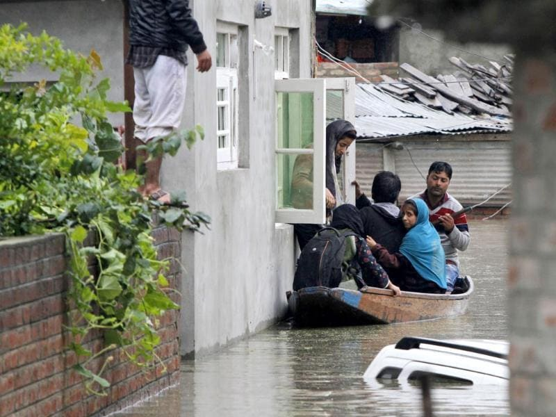 A Kashmiri girl boards a boat from the window of her home as she leaves her flooded neighborhood in Srinagar. (AP Photo)