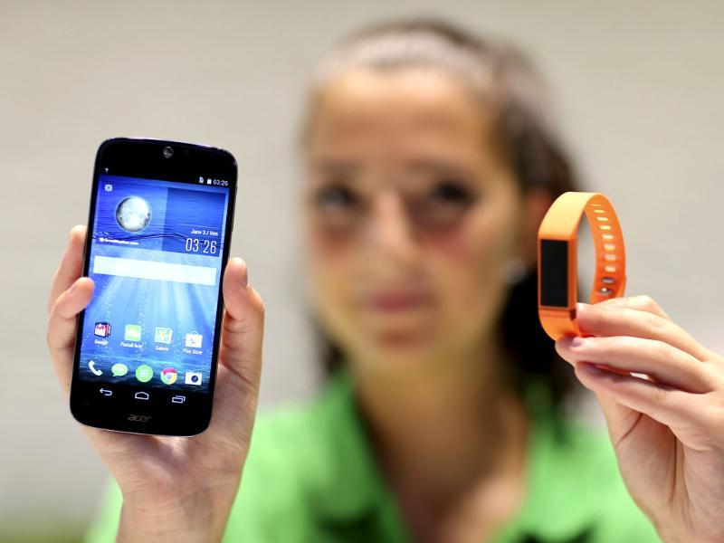 An employee shows Acer's Liquid Jade smartphone and the Liquid Leap smartband during the IFA Electronics show in Berlin. (Reuters)