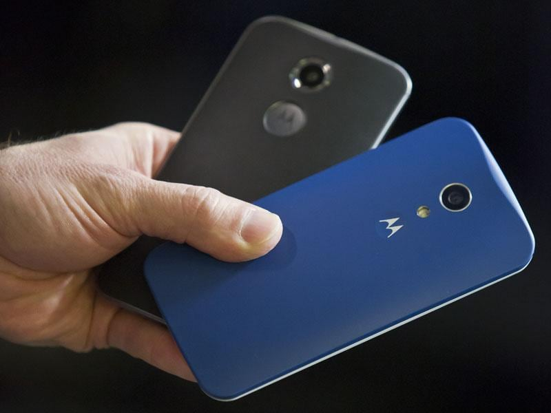 Steve Sinclair, Motorola's vice president of product management, shows the new Moto X, left, and Moto G phones during an interview in New York. (AP/Bebeto Matthews)