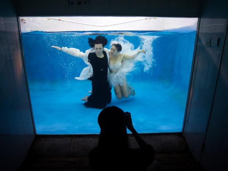 Qin Riyang (L) and Leng Yuting (C) pose underwater for their wedding pictures. Mr Wedding studio owner, Tina Lui, started providing underwater pictures four years ago. (AFP/Johannes Eisele)