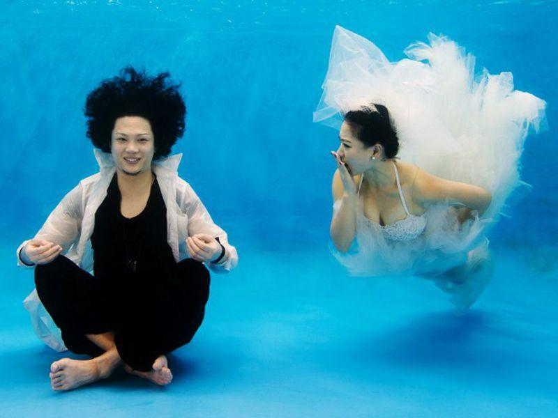 This photo taken on September 3, 2014 shows Qin Riyang (L) and Leng Yuting, both 26 years old, posing underwater for their wedding pictures at a photo studio in Shanghai, ahead of their wedding next year. (AFP/Johannes Eisele)