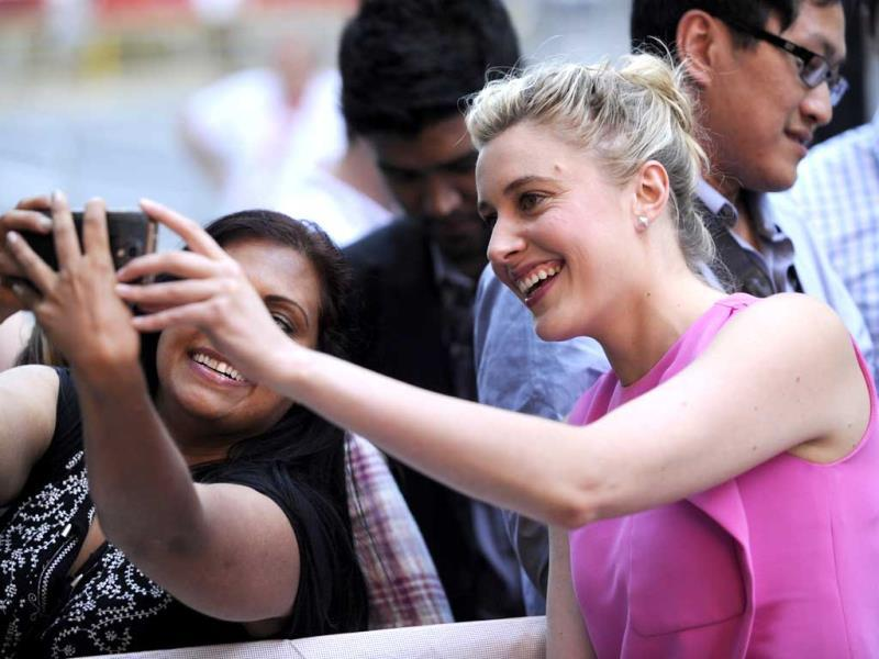 Greta Gerwig (right), takes a photo with a fan as she arrives at the premiere of The Humbling on day 1 of the Toronto International Film Festival at the Elgin Theatre on Thursday, September 4, 2014, in Toronto. (AP)