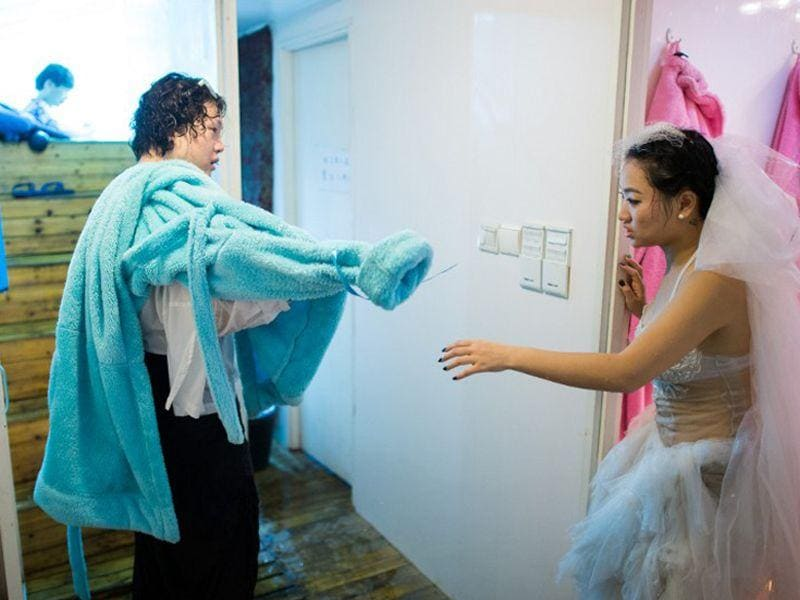 Qin Riyang (R) and Leng Yuting drying off after their underwater photoshoot at a studio in Shanghai. (AFP/Johannes Eisele)