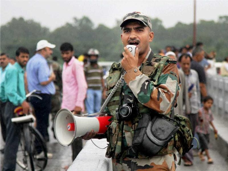 An army jawan alerts people over rising water level as heavy rains continue to lash Jammu on Friday. (PTI Photo)